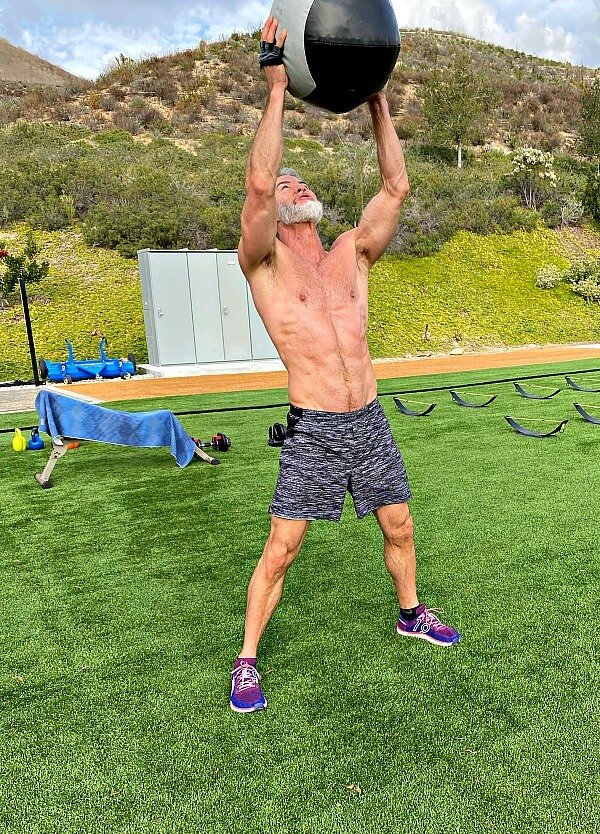 Man exercises with weighted medicine ball to train his back muscles.