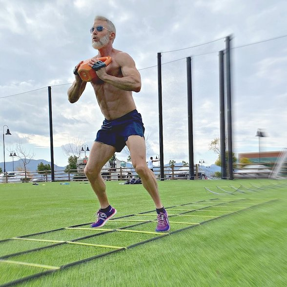 Fit man jumping holding kettlebell during leg workout.