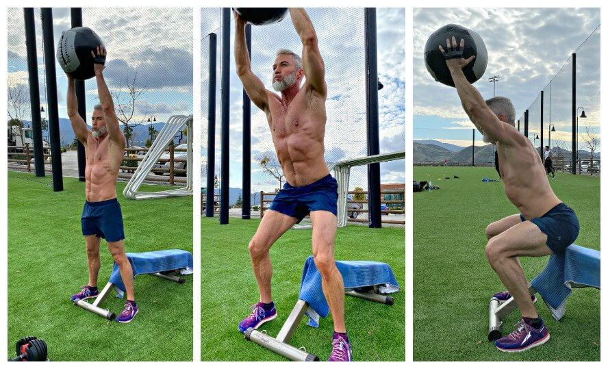 Athlete does overhead squat exercise with weighted medicine ball.