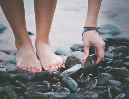 blote voeten met rode nagellak aan het strand meisje raapt steentje op