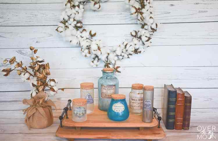 Old bottles distressed to look like potion bottles on a platter with a cotton wreath and old books.
