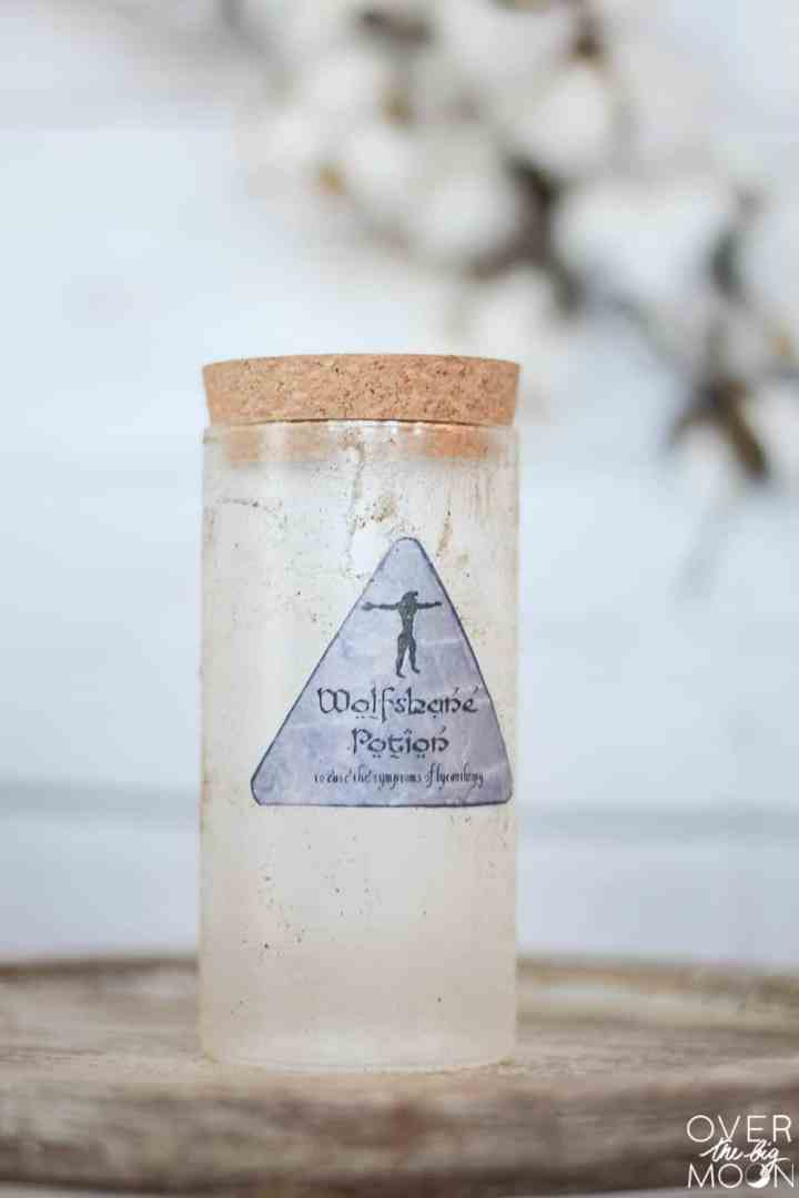 Wolfsheine Potion Bottle from Harry Potter. A clear bottle distressed with sand and glue to look old.