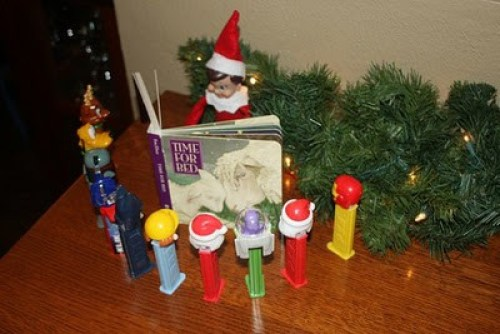 Elf reading a book to Pez dispensers