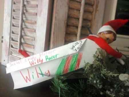 An Elf on the Shelf in a paper airplane by a window.