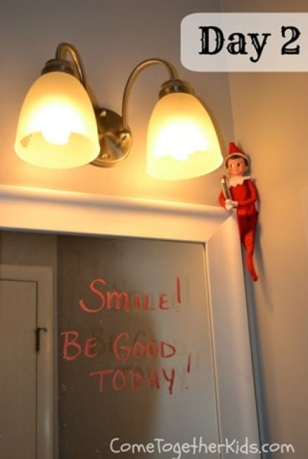 An Elf sitting on top of a mirror that says Smile! Be Good Today in lipstick.