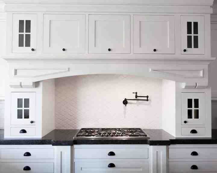A white kitchen, gas stove range.