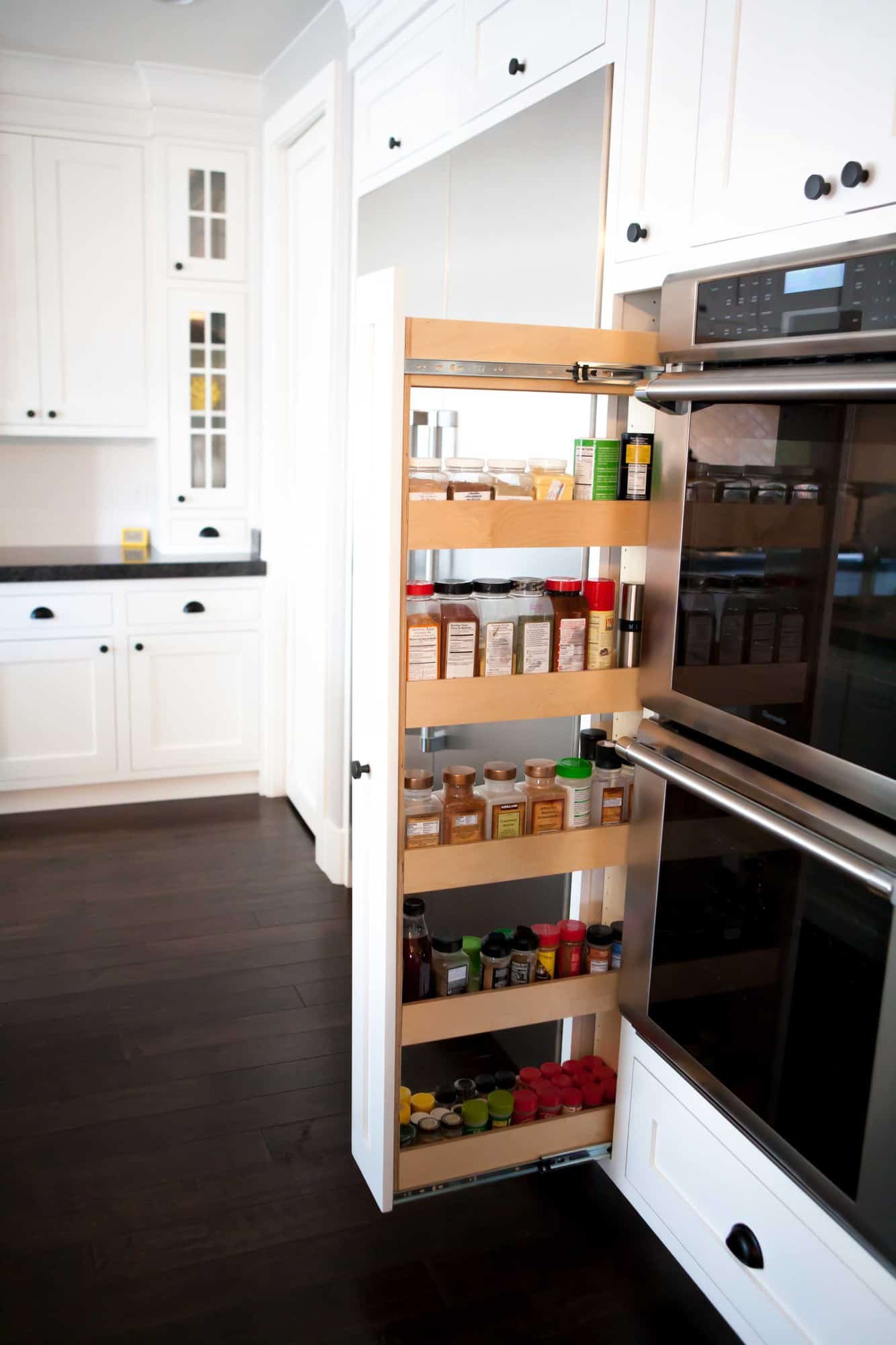 A rolling spice rack that is filled with spices that pulls out from the wall to the left of 2 ovens.