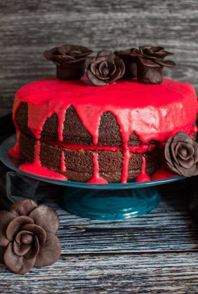 2 Layer Chocolate Cake with red dripping frosting drizzled over the cake to look like blood. Finished with chocolate fondant roses on the top and around the sides.
