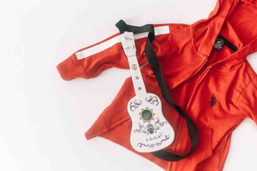 Red jacket that looks like Miguels from Coco's jacket. Plus a white ukulele with Coco decals on it!