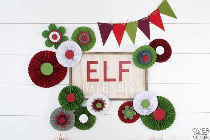 DIY Rosette Backdrop Tutorial - This one was made for my Elf Bake Shop Cookie Display! From overthebigmoon.com!