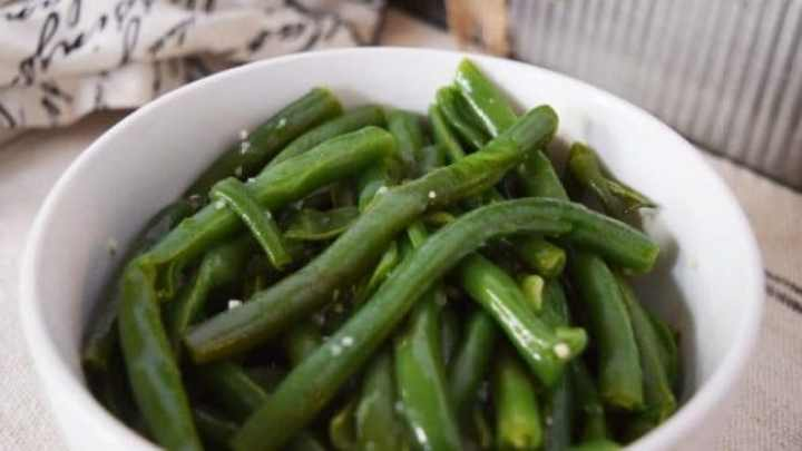 A bowl of green beans with dish cloth in the background.