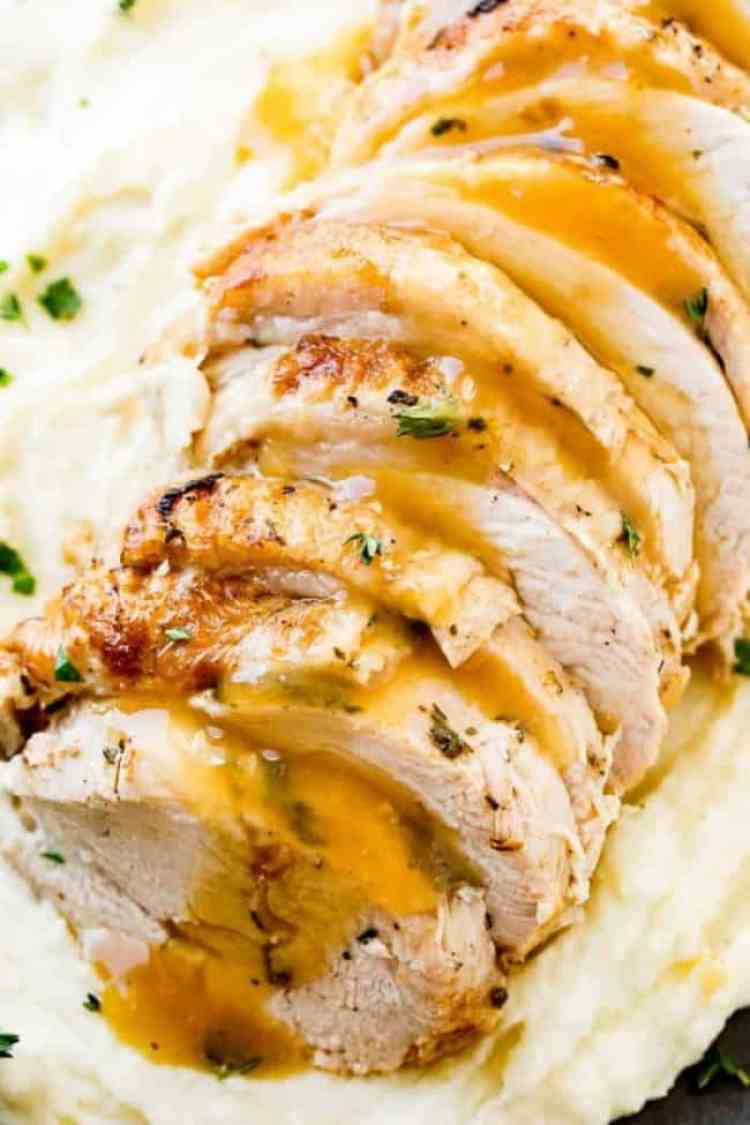 A platter of Turkey slices made in the Instant Pot. The Turkey is on top of a plate of mashed potatoes and then it's all drizzled with gravy.