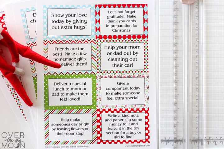 Printed Good Deed Cards next to a paper cutter and the Elf sitting to the left.
