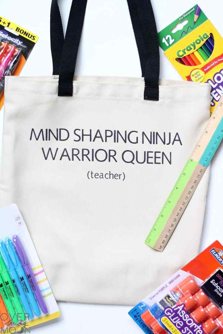 "A teacher Tote Bag that states 'Mind Shaping Ninja Warrior Queen (Teacher)"" on it, surrounded by school supplies!"
