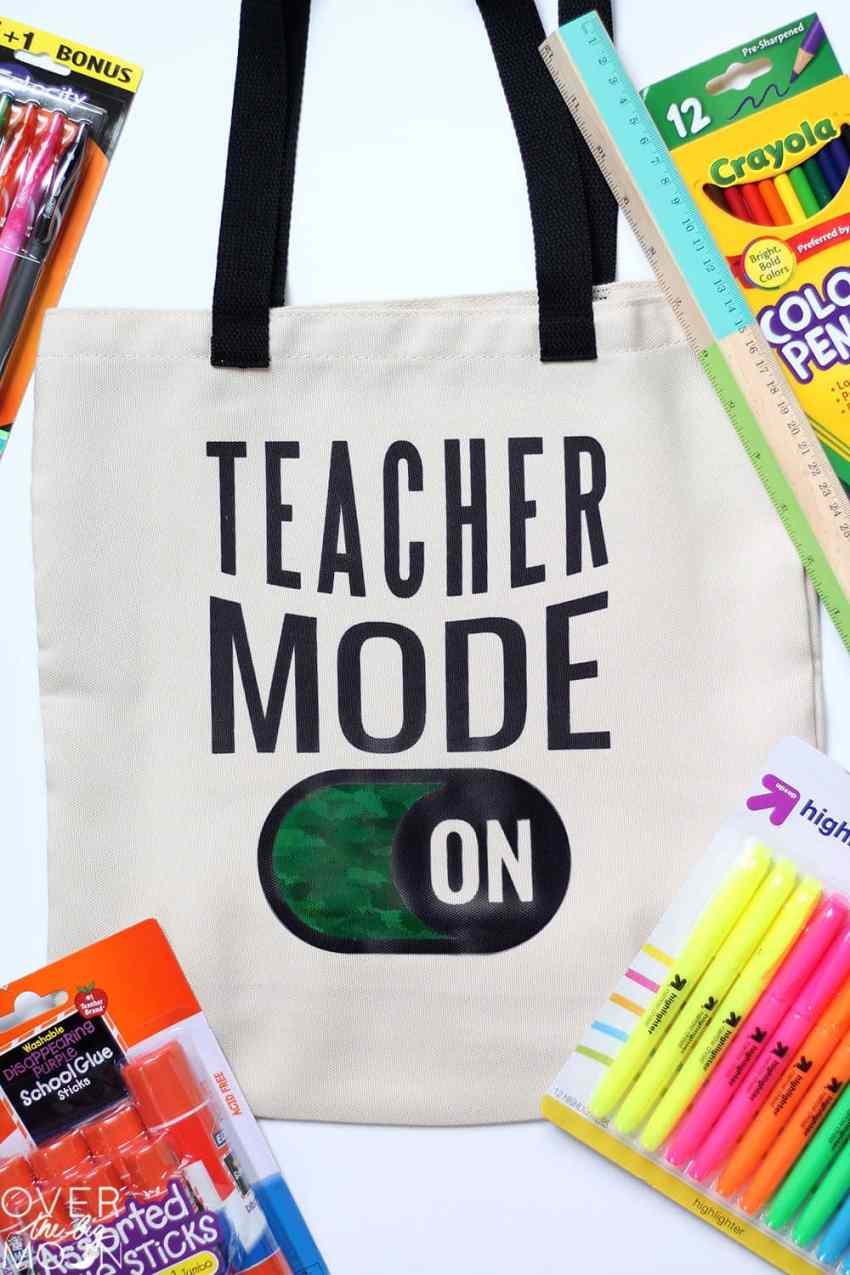 "Teacher Tote bag the says ""Teacher Mode On,"" surrounded by school supplies."