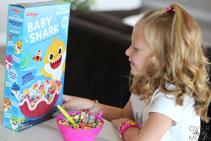 Little girl eating a bowl of Baby Shark cereal while looking at the box of cereal with a smile on her face!