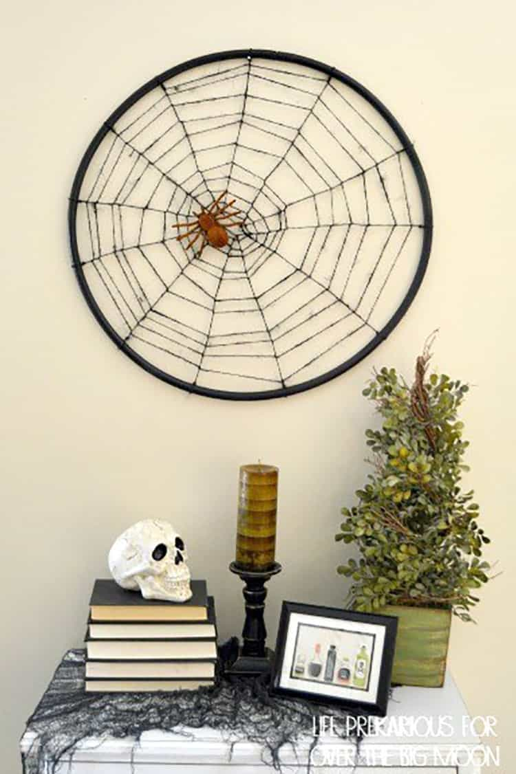 A DIY Spider Web made from Jute Twine and a Hula Hoop hanging over an entry way table decorated for Halloween.