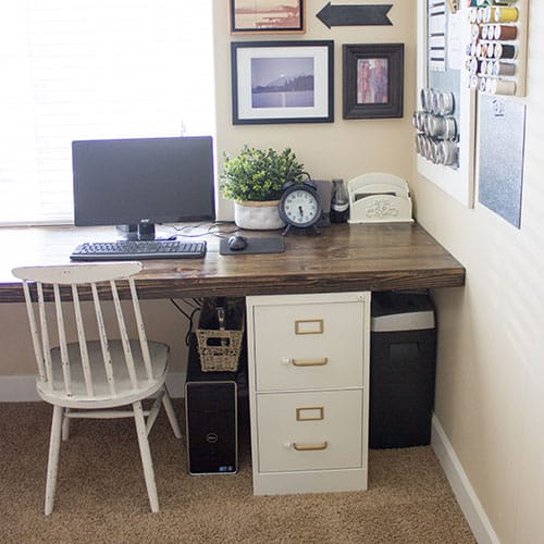 Desk made with a wood top and File Cabinet. There is a chair up to the desk, along with decorations on the table top and wall!