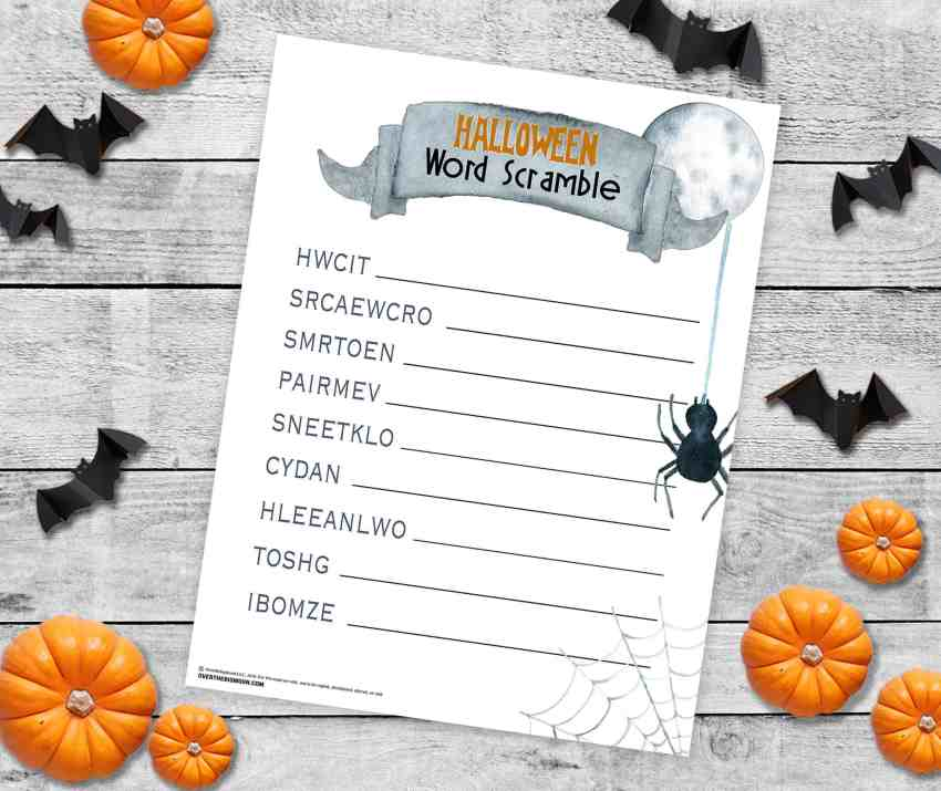 Halloween Word Scramble printed and laying on a table top covered in paper bats and mini pumpkins!