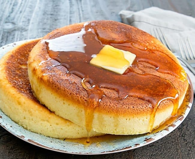 Two large Instant Pot Giant Pancakes, topped with a slice of butter and syrup.