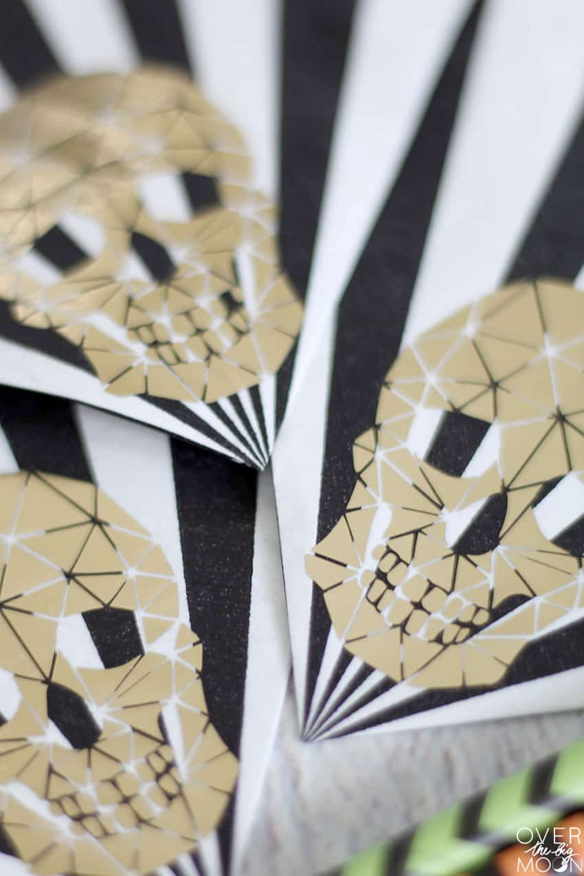 Up close picture of 3 napkins with Gold Foil Skulls on the corners.