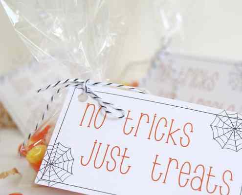 Candy corn in a bag, with a gift tag that says No Tricks, Just Treats on it. Candy corn is laying around the bags.