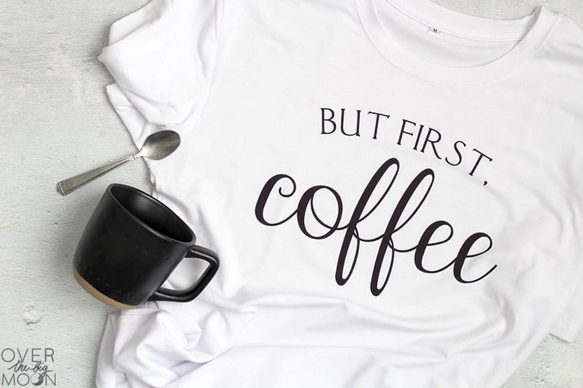"A white shirt that says ""But first, coffee"" on it. With a black coffee mug and spoon."