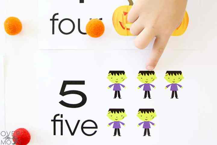A little hand using the #5 Halloween Counting Card.