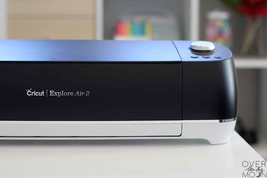 A Black Cricut Explore Air 2 Machine on the end of a white desk with a bookshelf behind it.