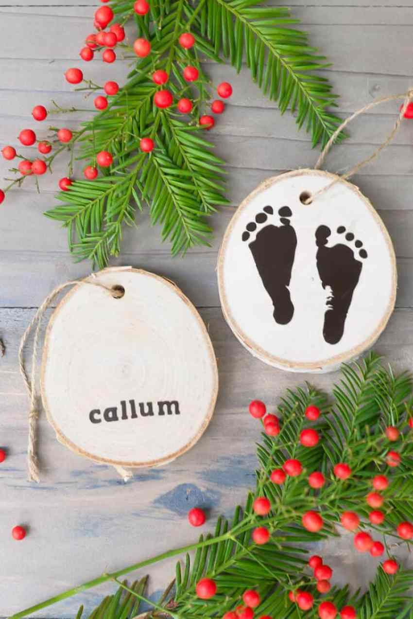 2 Handmade wooden ornaments made using a newborns footprints and their name.