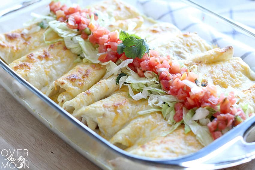 A pan of Honey Lime Chicken Enchiladas, topped with lettuce, pico and cilantro!