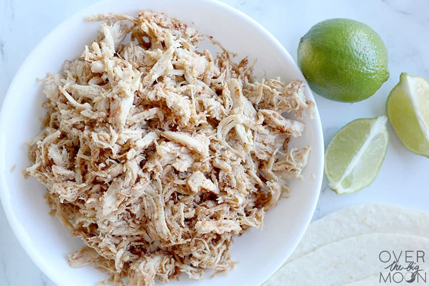 A bowl of honey lime shredded chicken, with some limes off to the side.