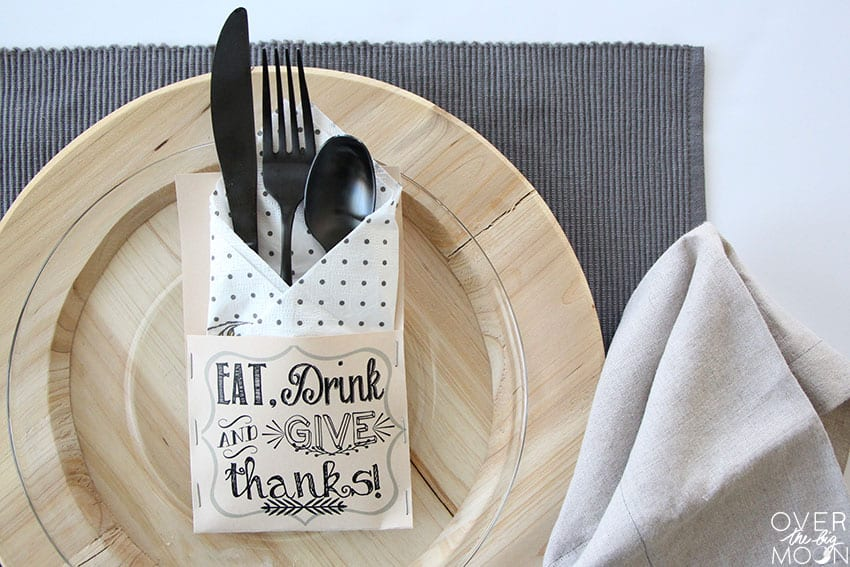 Printed silverware holder that says Eat, Drink and Give Thanks on it. Filled with a napkin and silverware, sitting on top of a plate.