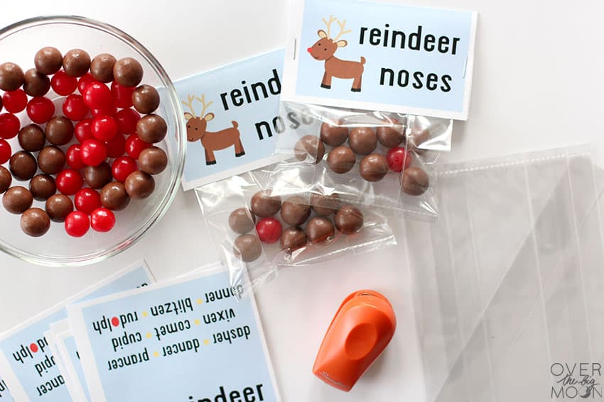 Filled Reindeer Noses treat bags next to clear empty bags, a stapler and a bowl full of whopper candies and sour cherry candies.