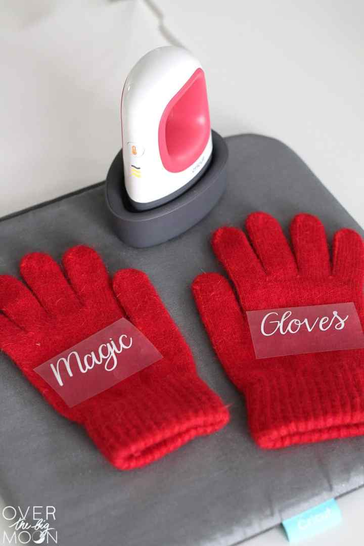 Red gloves with the words Magic Gloves placed on them ready to apply heat with the EasyPress Mini.