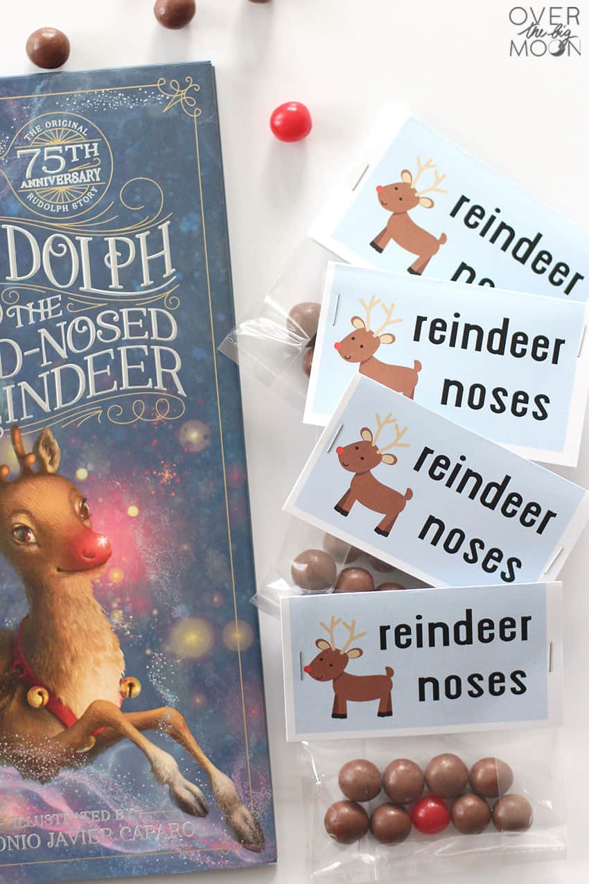 Reindeer Noses treat - whoppers and sour cherries in a bag, with a bag topper that says Reindeer Noses on it. Next to the book Rudolph the Red Noses Reindeer!