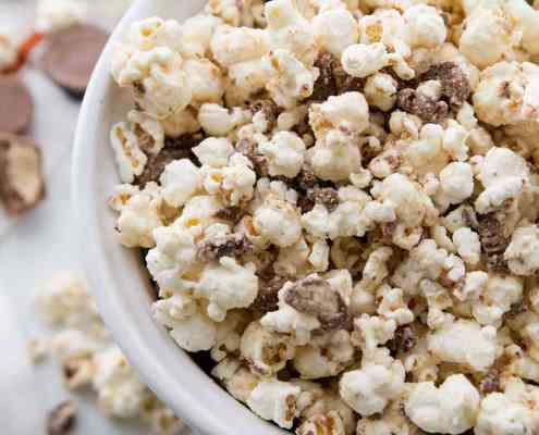 White Chocolate Peanut Butter Cup Popcorn in a white bowl, ready to eat!
