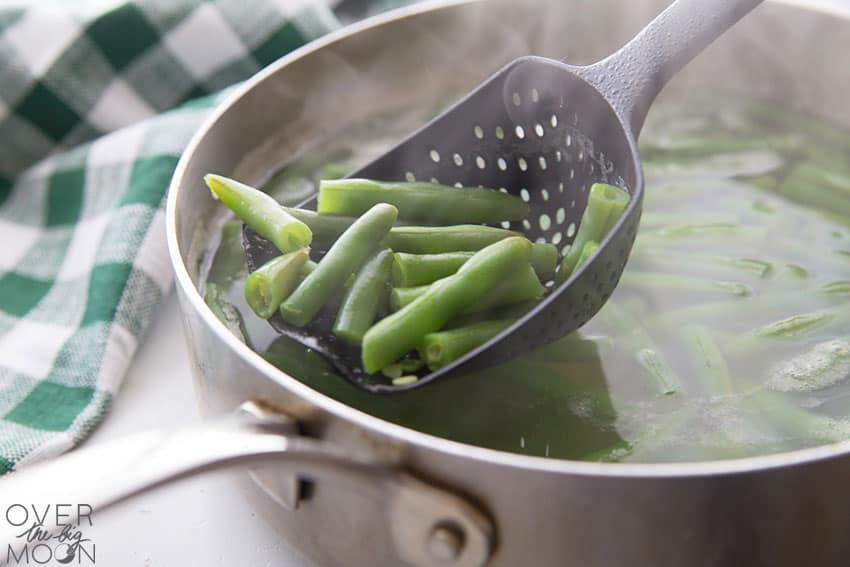 A pot of cooked green beans, being removed from the water with a slotted spoon.