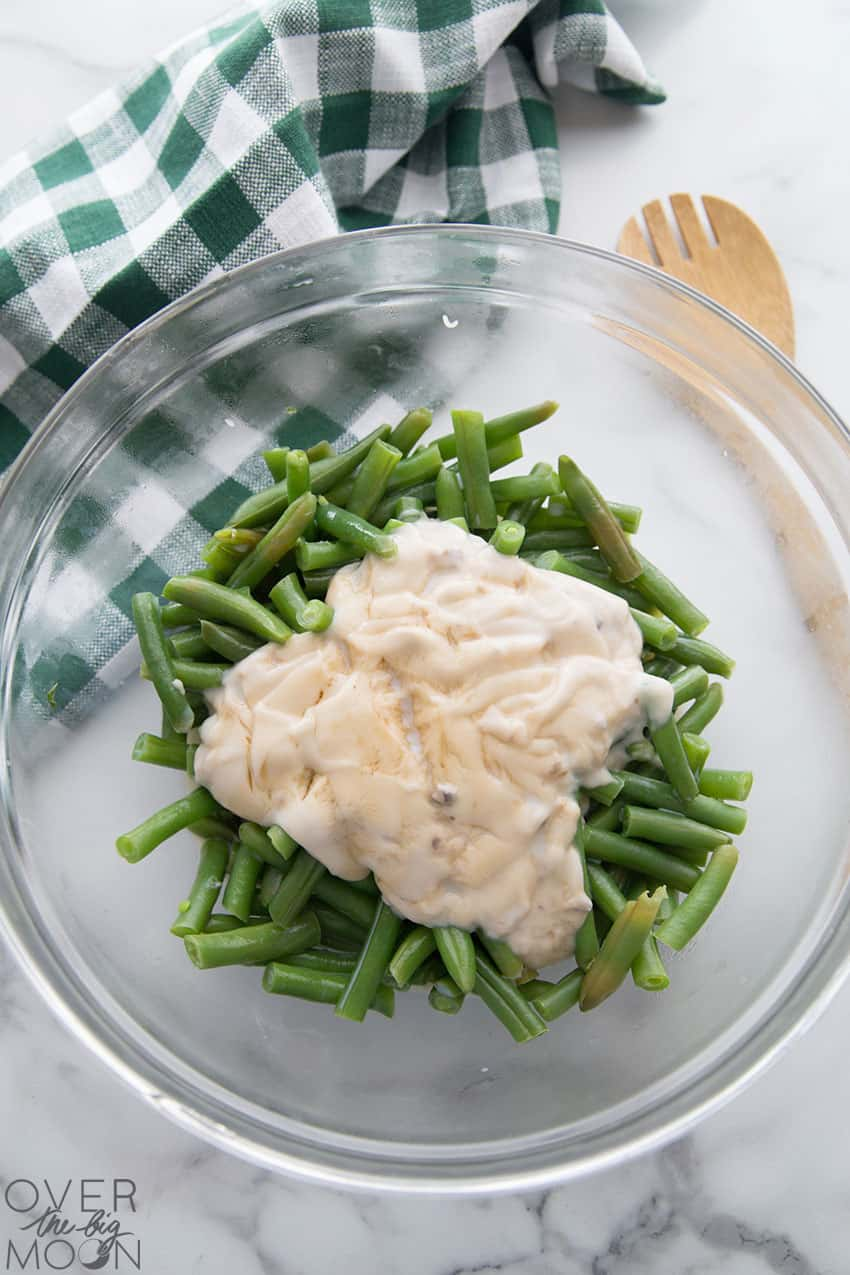 A bowl of green beans with a cream of mushroom soup mixture over the top.