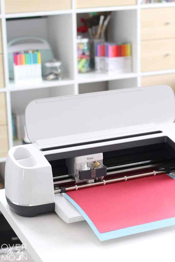 A Cricut Maker on the end of a white desk, with a lightgrip mat loaded into the machine with dark pink cardstock. In the background you see a bunch of shelves with craft supplies and drawers.