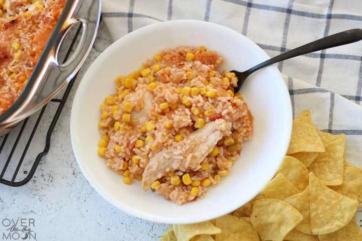 A bowl of Fiesta Chicken Casserole with tortilla chips off to the side and the pan of chicken casserole off to the left.