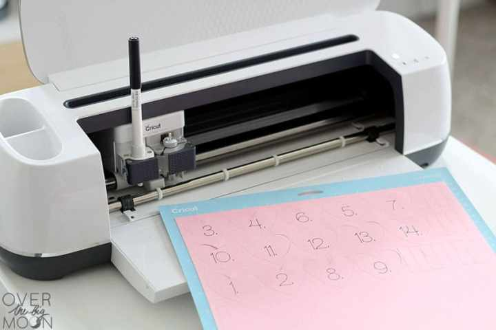 The Cricut Maker cutting machine with a black pen loaded in it. A blue lightgrip mat with light pink paper on it is laying in front of the machine showing that the machine just finished writing and cutting the heart designs out.