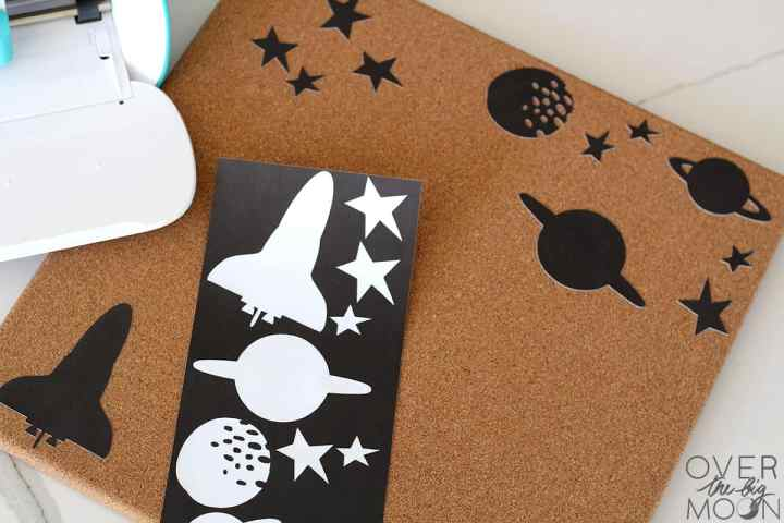Black Adhesive Paper with space stickers removed from it and applied to a cork board.