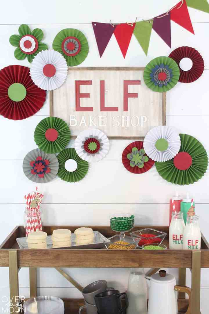 A cookie station bar, stocked with cookie decorating supplies. With a detailed backdrop on the wall that says Elf Cookie Station and a ton of colorful rosettes and a bunting.