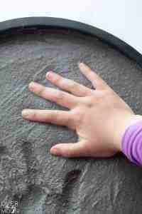 A little hand placing a handprint into the wet plaster of the stepping stone.