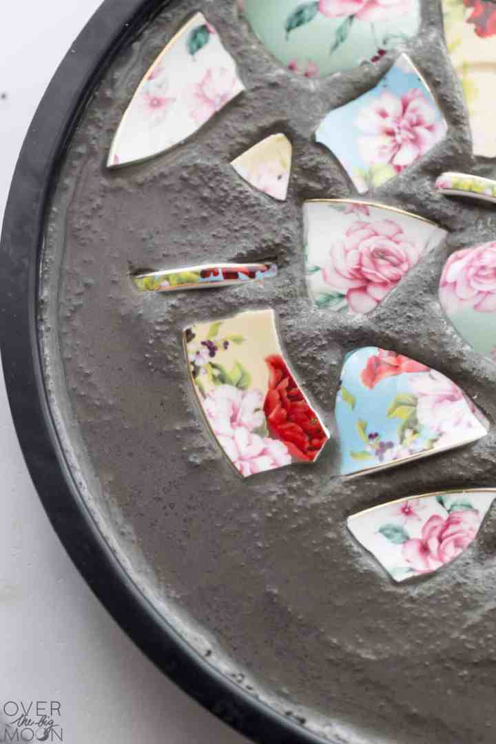 Pieces of broken china being put into wet plaster.