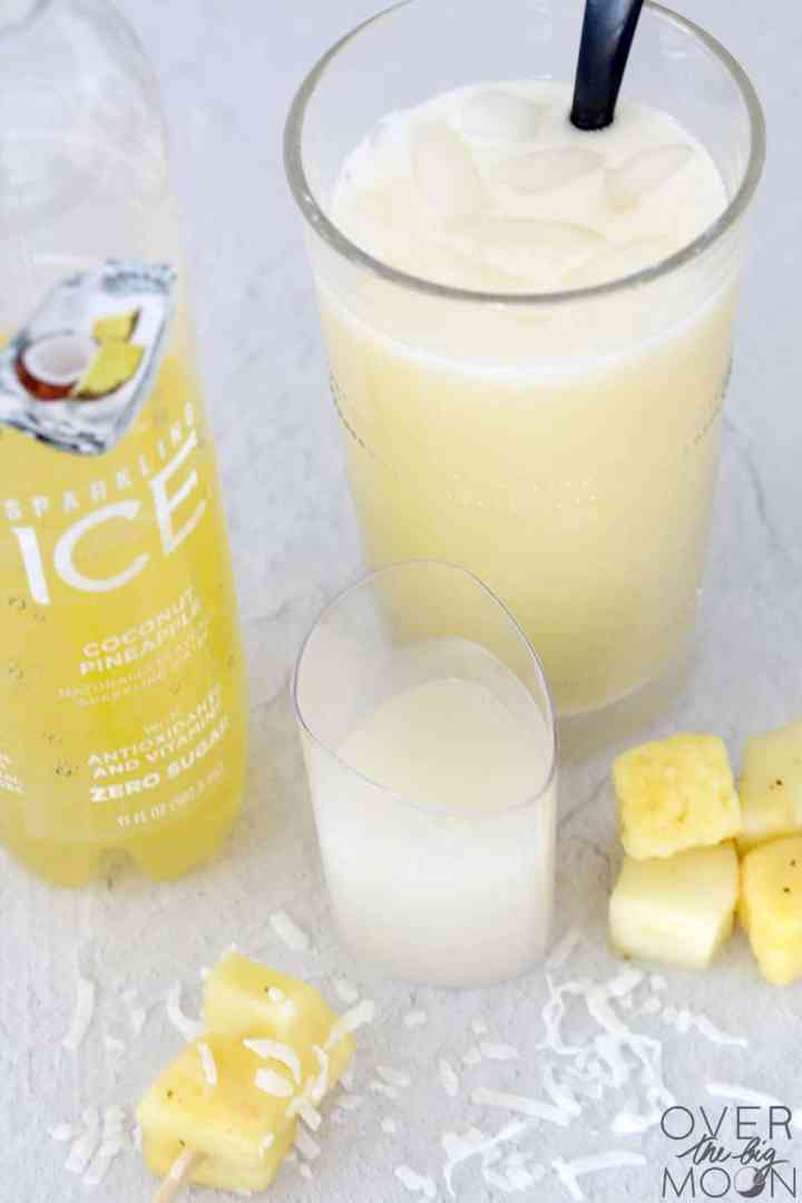 A glass of Pina Colada with a bottle of sparkling ice. There are chunks of pineapple and coconut flakes around the glass and a container of cream of coconut.