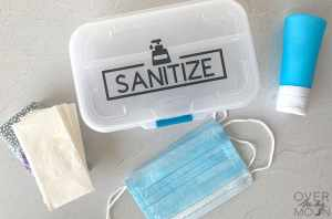 Clear container with the word Sanitize on it with hand sanitizer, face masks and tissues around it.