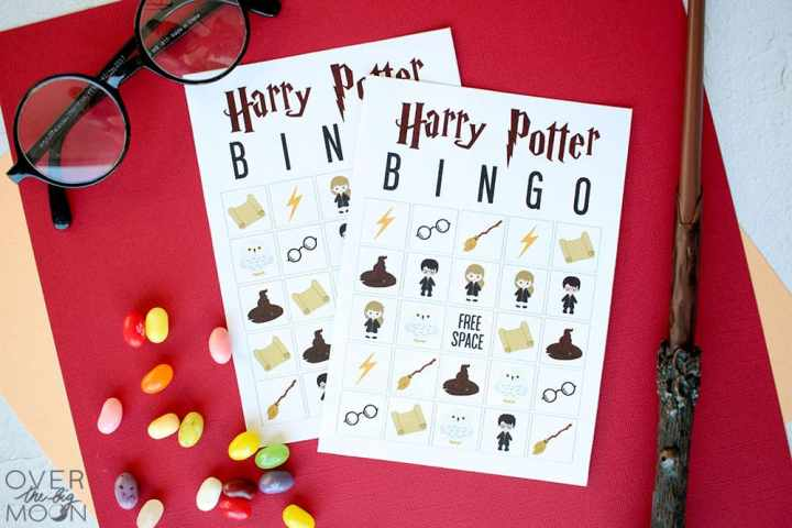 Two Harry Potter Bingo Cards on a red table, with Harry Potter glasses, jelly beans and a magic wand to the side.