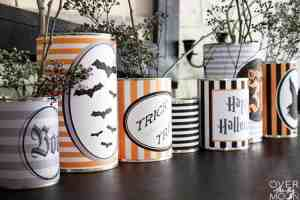 7 tin cans on a black tabletop that are wrapped in Halloween Can Wrappers with baby breath in them that is spray painted black.